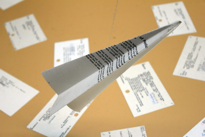 A close up of a paper airplane over index cards.