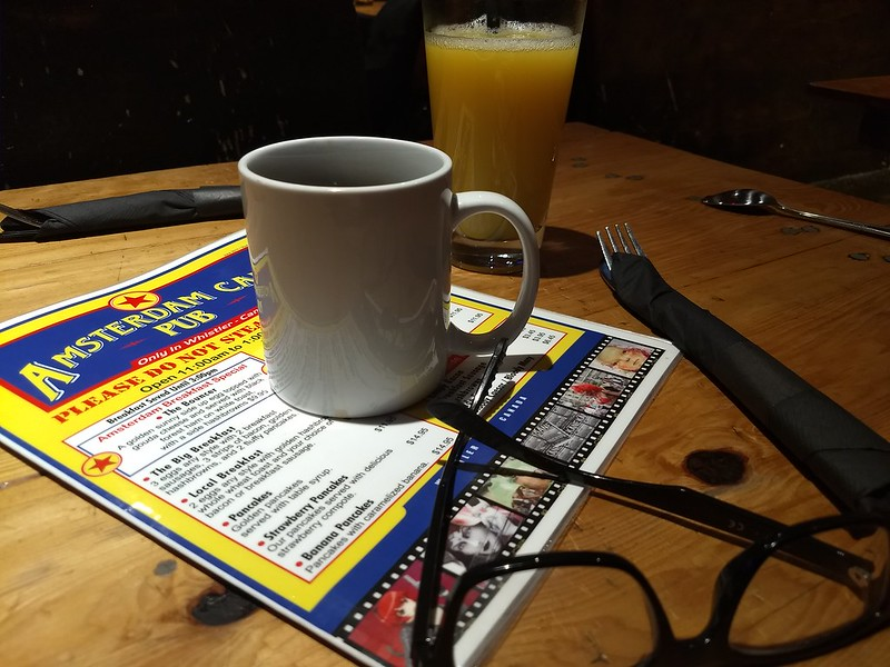 Picture of cofee on a breakfast menu with glasses in the foreground.