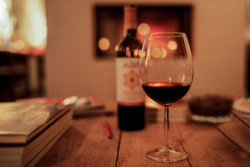 Glass of red wine in the foreround on a table.