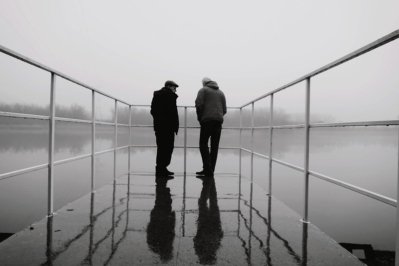 Two friends talking at the end of a dock. Black and white photo.