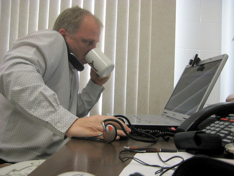 Picture of Dean Shareski at a desk drinking coffee while working at a laptop.