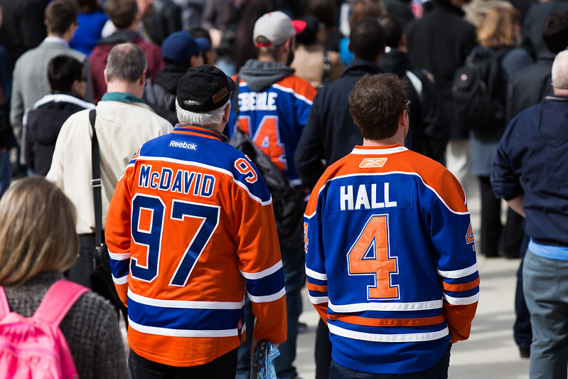Image from 2016, two fans with backs to us. One has a McDavid 97 jersey, the other a Hall 4 jersey, walking through a crowd.