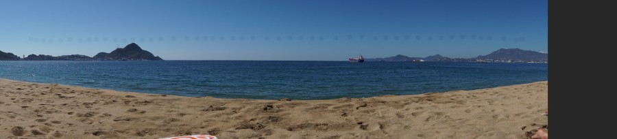 Panoramic shot at Las Brisas beach in Manzanillo. Sand in the foreground with a view of the bay, some ships visible.