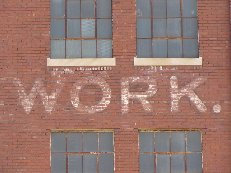 "The word "" Work.""painted on a brick building."