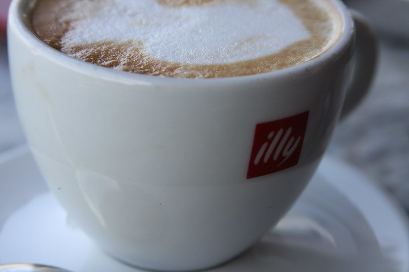 "Close up of a cappucino in a ""illy"" mug."