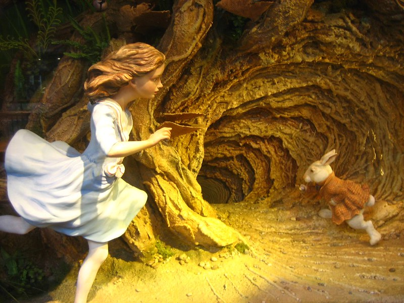 An image of Alice chasing the rabbit down the rabbit hole.