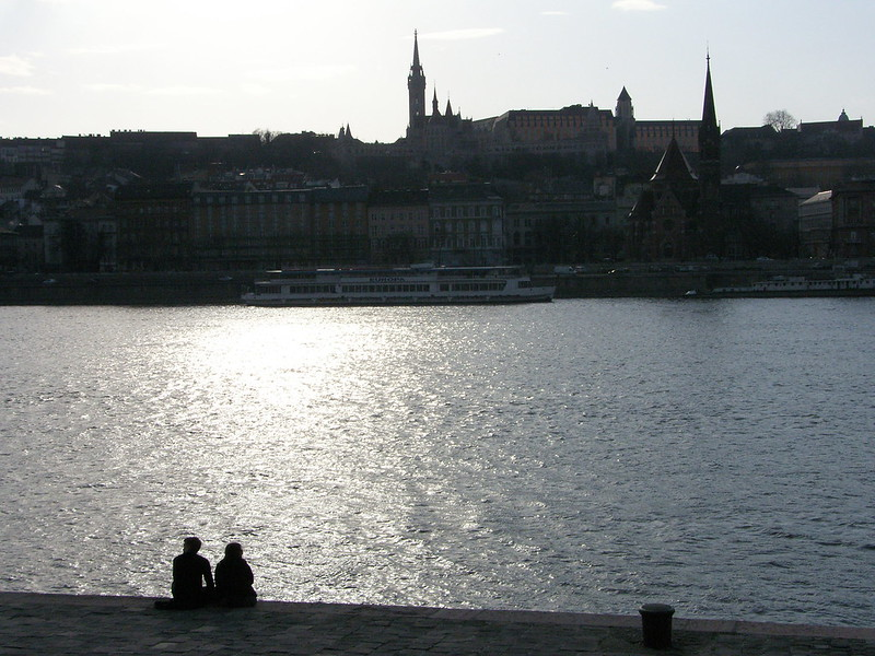 A couple sitting on a pier at the river through Budapest.