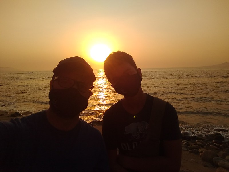 Silhouetted selfie with my son with the setting sun in the background over the ocean.
