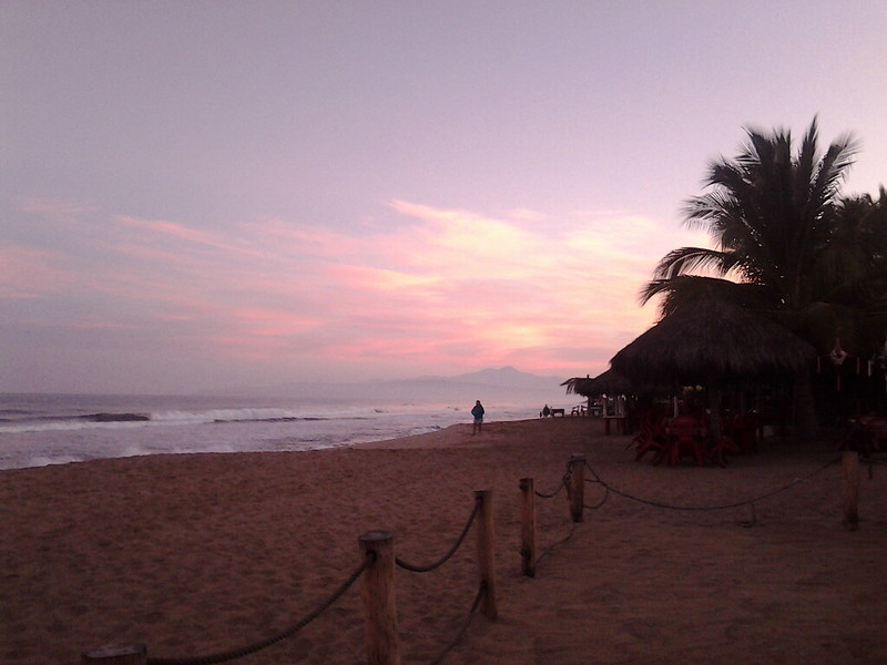 Sunrise on the beach at Rincón de Guayabitos, Nayarit. Waves crashing in the background with the fenced off area of the beach and palapas in the foreground.
