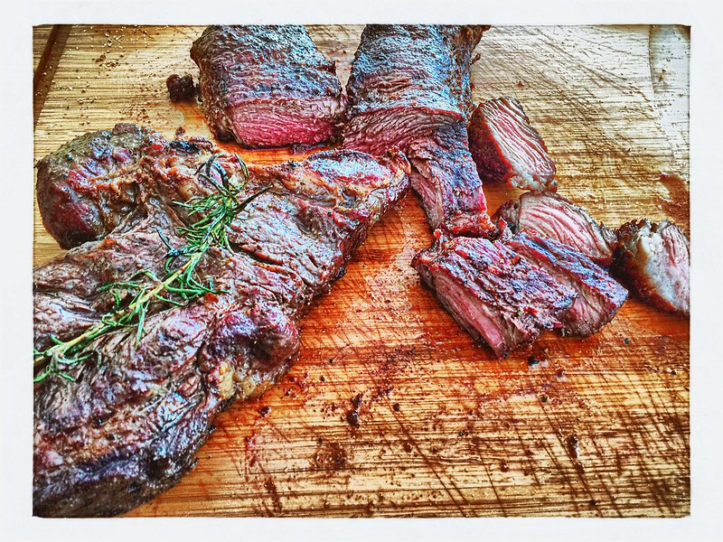 Freshly grilled and slided skirt steak on a wood cutting board.