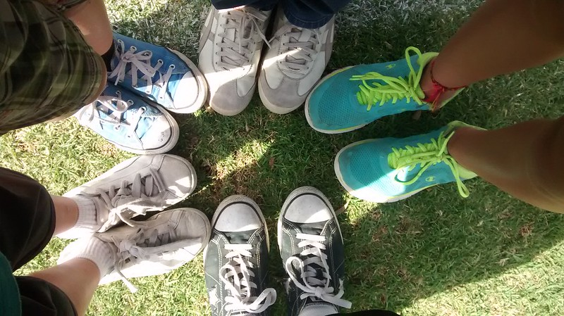 Picture from above of five people in running shoes all touching at the toes.