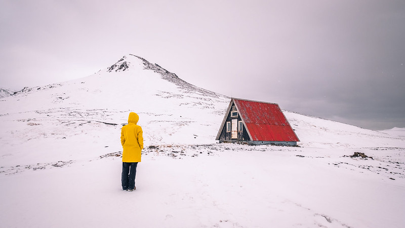 Picture in Iceland of a small a-frame house with a red roof, snof all around, and a person with back to the photographer looking towards the house with a bright yellow jacket on.