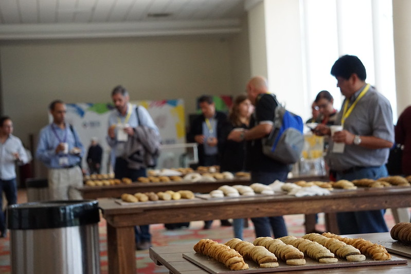 Close up of cookies at a break during an event with out of focus attendees in the background.