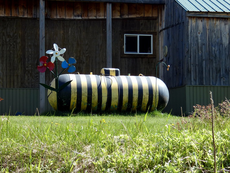 Picture of propane tank painted yellow and black, decorated as a bumblebee with plastic flowers in front and house in the background.
