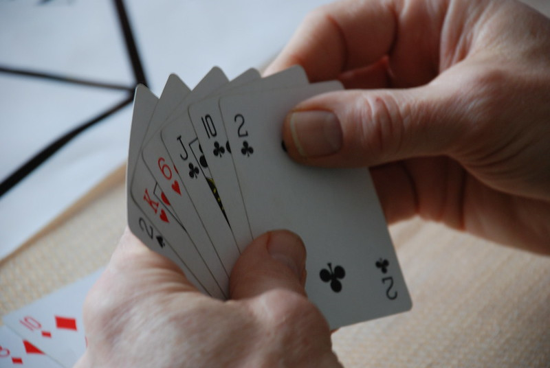 Close-up shot of six playing cards (2 of spades, King of hearts, 6 of hearts, Jack of clubs, 10 of clubs, 2 of clubs) behind held in two hands.