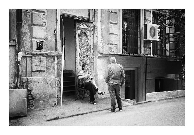 A black and white street image of a woman seated just outside a doorway talking to a man with his back to us standing on the edge of the road. Older building in the background. Apparently the shot is taken at Tbilissi, Georgia.