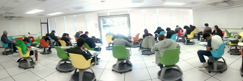Picture of students in colourful chairs with their backs to the photographer taking an exam, windows in the distance with light streaming in.