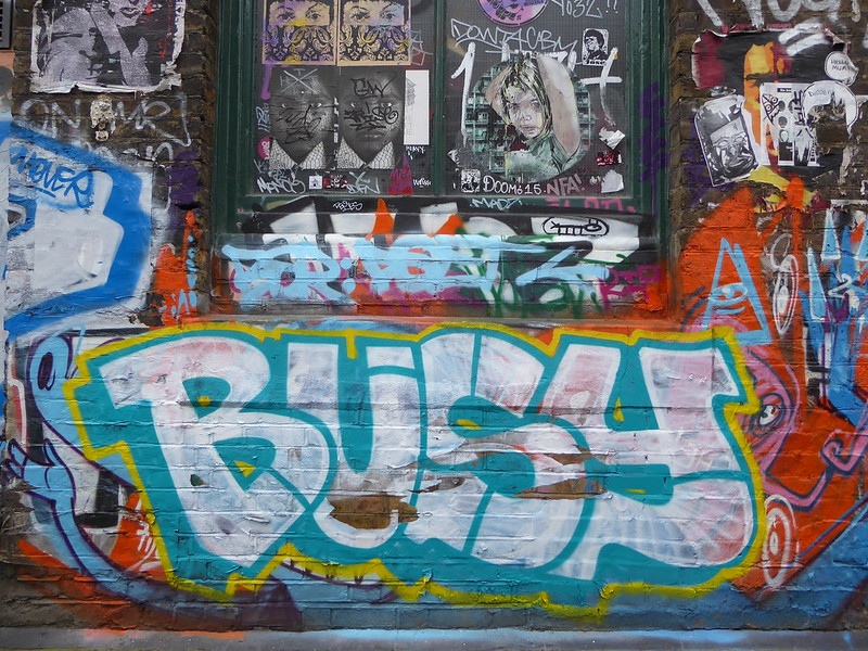 """Graffiti brick wall with the word """"Busy"""" the central focus."""