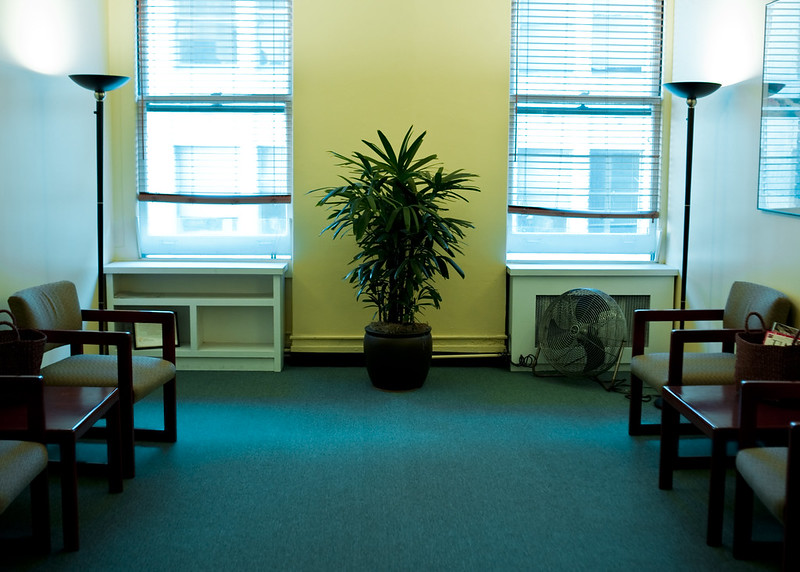 A typical doctor's waiting room. Two windows with a plant in between them; chairs on each wall; lamps in the corner between windows and chair.