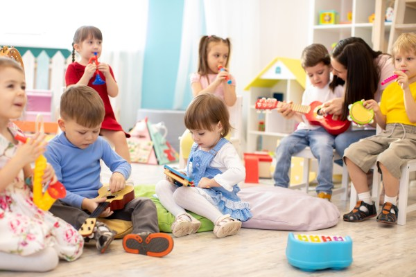 Kindergarten teacher with children on music lesson in daycare. Little kids toddlers play together with musical toys.