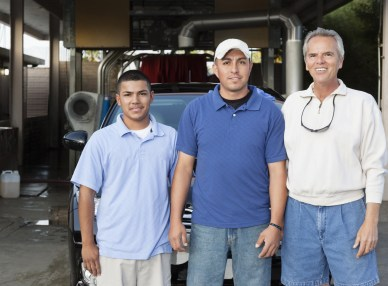 Car wash owner standing with newly hired employees.