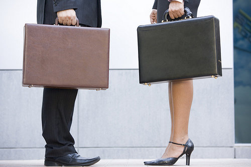 Two businesspeople holding briefcases outdoors
