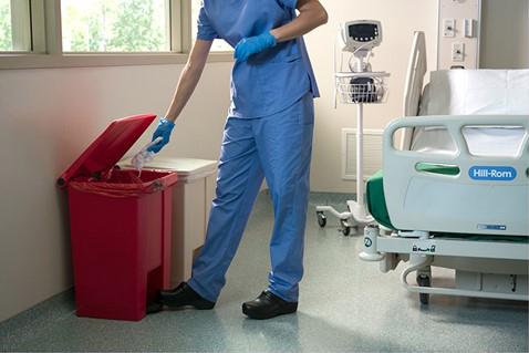 Personne utilisant une poubelle sans contact Step-On de Rubbermaid Commercial Products dans une chambre de patient.