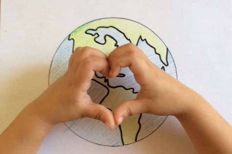 little hands making heart over earth drawing