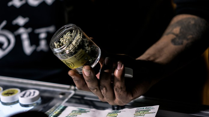 budtender showing jar of marijuana