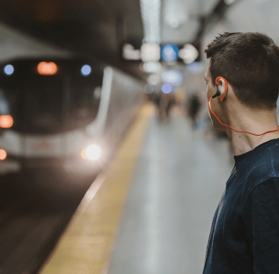 Man waiting for underground with headphones on