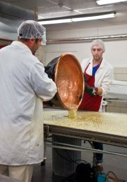 Owner Greg Dauphin (left) and candymaker Shawn Freeder pour the Sugar Puff base onto the cooling table.
