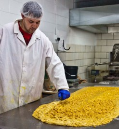 Paul quickly adds more cashews through the top of the brittle.
