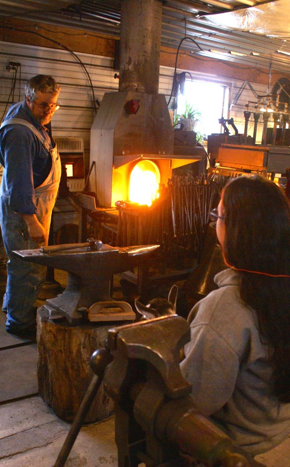 Doug and Danielle talk over the day's work while the forge warms to working temperatures.