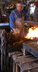 Doug re-warms a workpiece in the forge.
