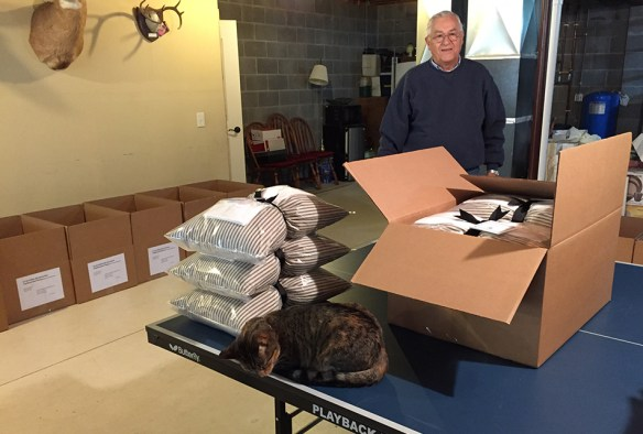 "The couple's cat gets in on the ""quality control,"" as Allan looks on."