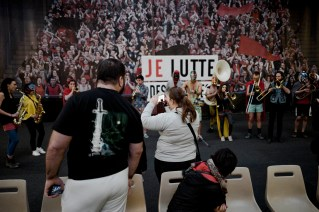 A woman takes a picture as musicians perform in the background during the wrestling charity gala in Ivry Sur Seine, south of Paris, Saturday, Feb. 24, 2018.