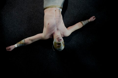 Wrestler Ace Angel lies on the ground after being thrown out of the ring at the wrestling charity gala in Ivry Sur Seine, south of Paris, Saturday, Feb. 24, 2018.