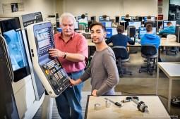 CNC- Technik — Kursleiter Raimund Schroeder erklärt dem Auszubildenden Feinwerkmechaniker Daniel Zuccarello die Maschinenbedienung. Im Hintergrund lernen die anderen Kursteilnehmer das Programmieren von Maschinen.