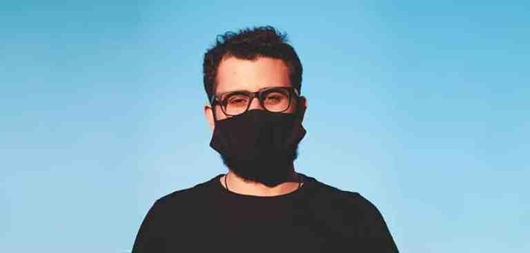 Lojista virtual usando máscara durante a pandemia, procurando por dicas de bem-estar