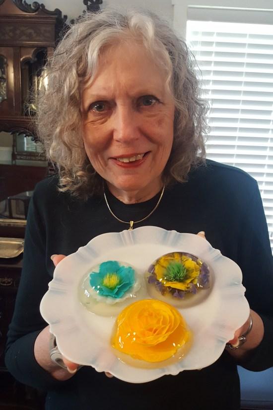 Susan Hood holding a plate with 3 gelatin art desserts.