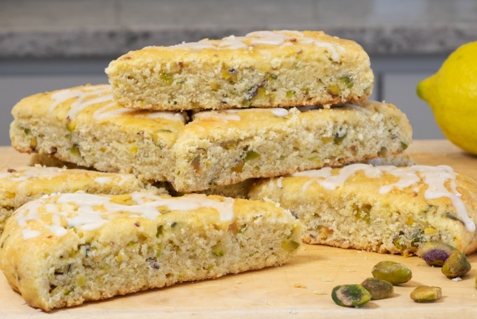 Stacked gluten-free pistachio scones with lemon glaze drizzled on top.