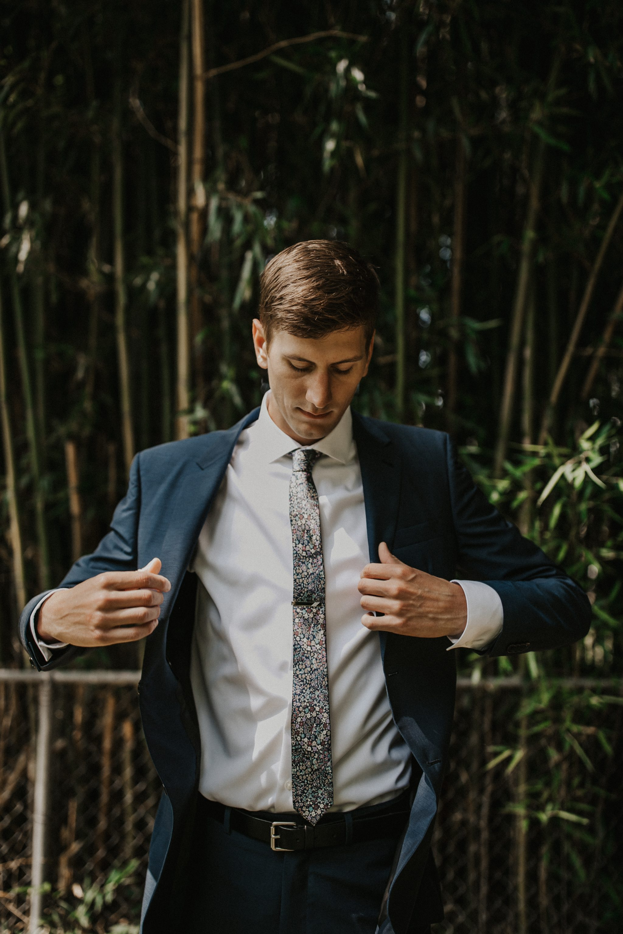 Southern groom puts on navy, custom jacket by Indochino in garden