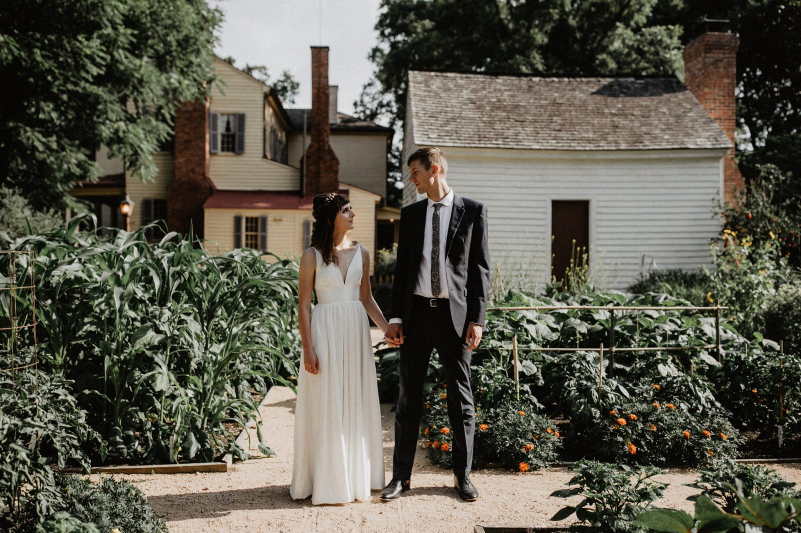 Sustainability-focused bride and groom look to each other as they stand side by side and hold hands in Historic Mordecai Park's garden.