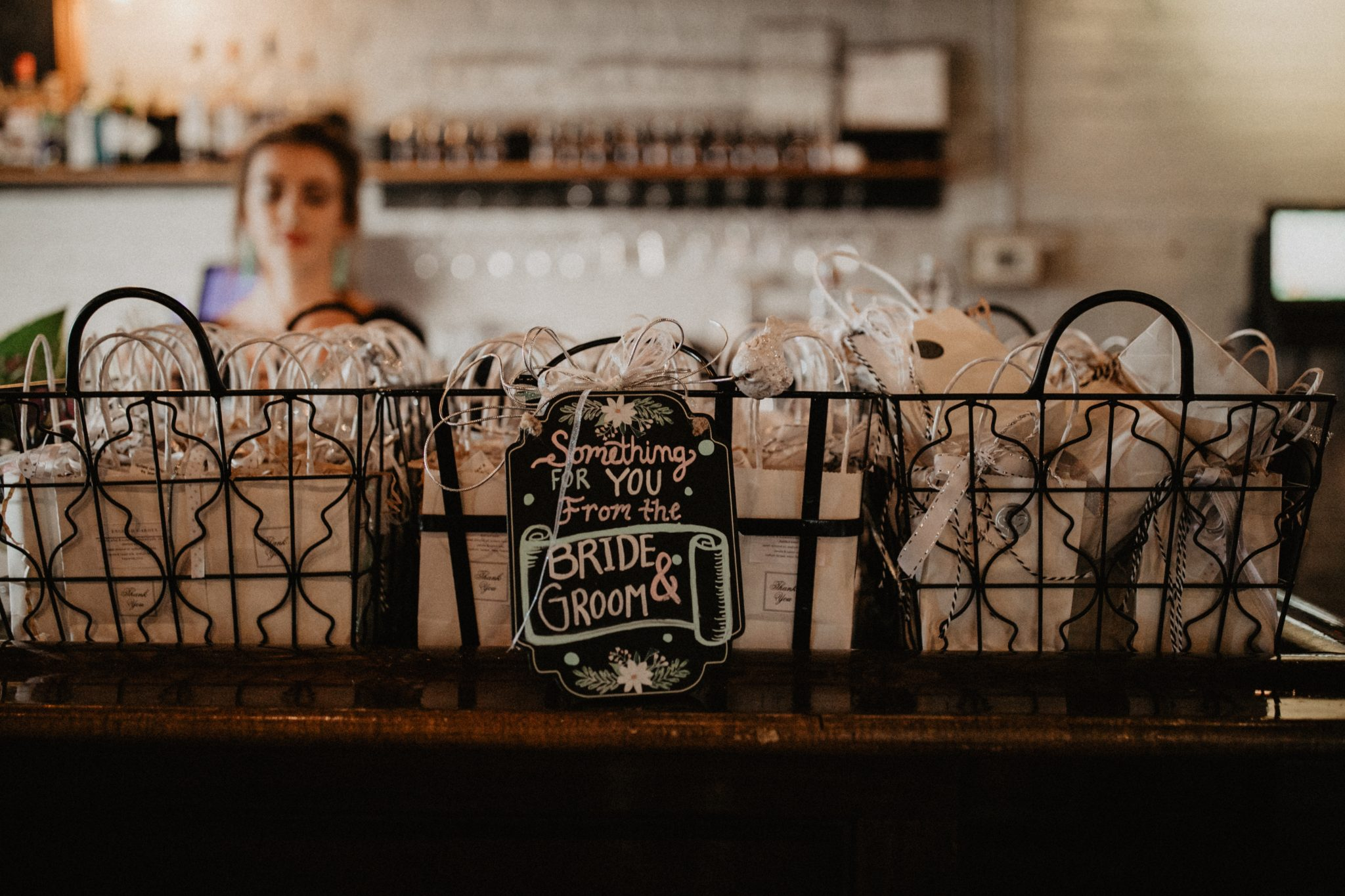 Wire baskets filled with handmade soaps in white paper bags as wedding guest gifts.