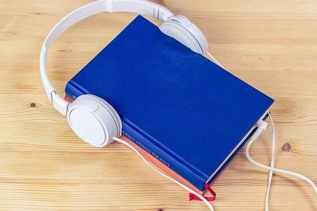 Audiobook graphic - book with headphones. Stock image.