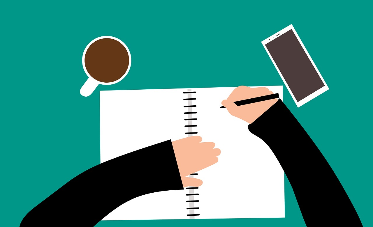 Stock image from Pixabay of a person writing in a notebook