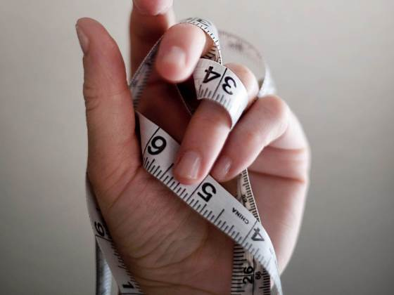 A hand holding a tape measurement representing losing weight