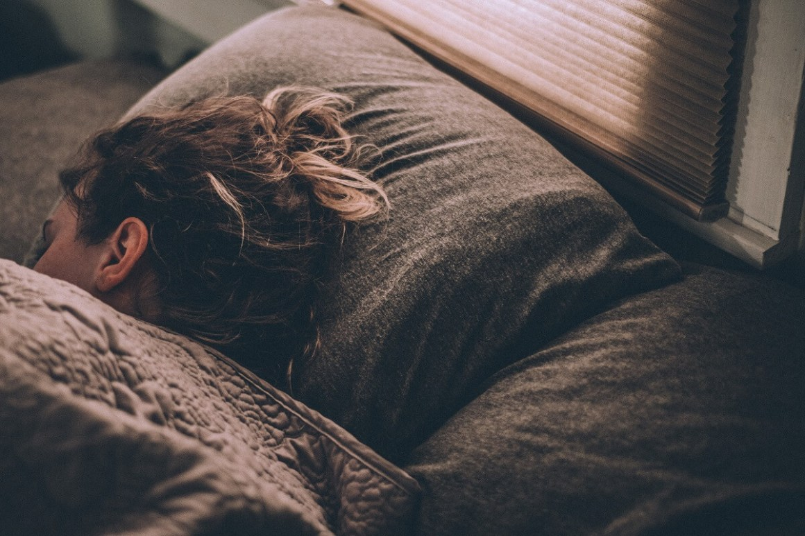 Frau schläft im Bett in einem abgedunkelten Raum
