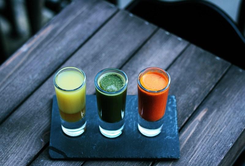 Drei klare Shotgläser mit Flüssigkeiten in unterschiedlichen Farben