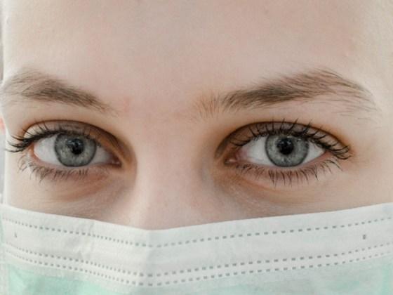 Frau mit blauen Augen und Mundschutz um sich vor Corona zu schützen
